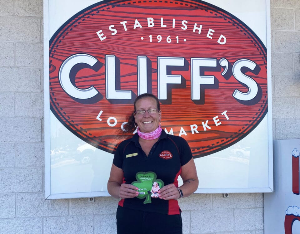 Cliffs employee holding MDA shamrock in front of sign